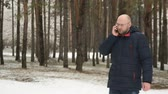 Businessman walk in winter along pine park and stops to make important call