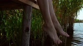 привлекательность : Legs of young woman over river water. Vintiage appearance