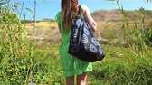 привлекательность : Young woman tourist throws bag on her shoulder and walks along green grass