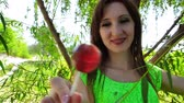 привлекательность : Young woman under tree licks candy on stick. Close up