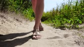 привлекательность : Young woman is walking on sand. Close up view on legs