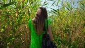привлекательность : Young woman with bag on her shoulder makes her way through thickets of reeds