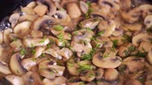 wok dishes : Brown champignons in oil on frying pan are sprinkled with dill and herbs