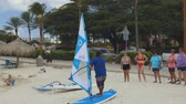 Video showing a instrustor giving short explanations regarding windsurfing on sandy beach of Atlantic Ocean. Aruba. Oranjestad. 10092019 Stockvideo