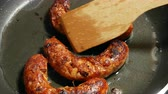 bem feito : Overhead Closeup frying link sausage fast food in cast iron skillet Vídeos