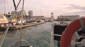 cais : The ship enters the harbor, view from the stern of the ship. Seaport of Sochi. Lifebuoy in the foreground
