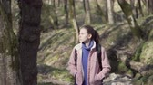 Girl traveler with a backpack travels in the forest Стоковые видеозаписи