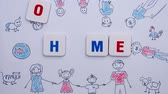 aletsiz : Red and blue letters form the word home on the background of drawing of family. Stop motion