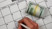 финансы : Money near the written word TAXEX on the calendar. Slow motion Стоковые видеозаписи