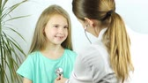 Pediatrician talks to smiling girl and listenes heart beat using a stethoscope