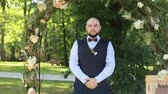 groomsmen : Rich stylish groom in blue suit and with bowtie waiting bride near the wedding arch Stock Footage