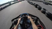 go cart : tree drivers drive go kart, Karting filmed from the drivers view, Man holds the steering wheel with his hands, Man drives go kart on track
