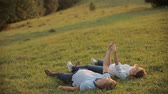 romance : Charming couple in love and lie on the grass in the mountains on sunset