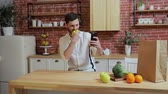 prohlížení : Man browsing on mobile phone at home kitchen. Handsome young man browsing on smartphone smiling happy. A man eats an apple and make photo.