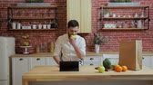 prohlížení : Man browsing on tablet PC at home kitchen. Handsome young man browsing on Tablet PC and smiling happy. A man eats an apple.