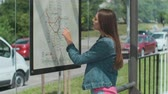 reisplan : Woman looking on the scheme of public transport while standing at the tram station outdoors.
