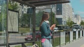 смотреть : Young stylish woman waiting for the public transport while standing at the modern tram station outdoors.
