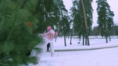 若い : Mom and little daughter playing peekaboo from behind a bush in the winter forest 動画素材