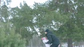 Slow motion, dad throws his daughter up to the sky in the winter forest.
