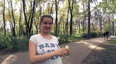 若い : Charming pregnant girl playing with soap bubbles in the park 動画素材