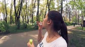 Charming pregnant girl blows soap bubbles in the park on the bench