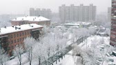 Snowfall in the city, shooting from a tall building, trees, lights, roofs of houses and cars covered with snow