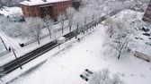 Snowfall in the city, big snowflakes are slowly circling, shooting from a tall building, pedestrians walking along the sidewalks, trees, lanterns, roofs of houses and cars covered with snow Stock Footage