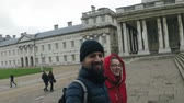 A guy in a dark blue hat and jacket with a beard and long hair walks in a park in London near a colonnaded building with a girl in a red down jacket with a capishon and smiling