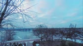 Time laps, view of the Paton Bridge over the Dnieper River in Kiev in early spring, red clouds from sunset, snow
