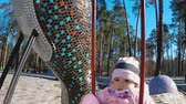 A little girl in a pink jacket and striped hat is riding on a swing in a park with tall pine trees in early spring in sunny weather