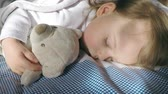 Beautiful little girl with blond hair sleeping on the bed and lit by the sun with a teddy bear in her hand