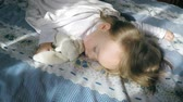 Beautiful little girl with blond hair sleeping on the bed and lit by the sun, hugging a plush bunny