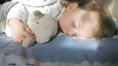 若い : Cute little girl with blond hair sleeping on the bed and lit by the sun with a teddy bear