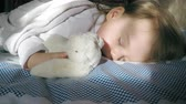 Cute little girl with blond hair sleeping on the bed and lit by the sun with a teddy bunny