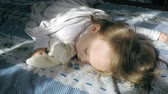 Cute little girl with blond hair sleeps sweetly on the bed on her tummy lit by the sunshine with a teddy bunny hugging