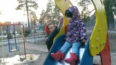 A young beautiful mother takes care of her daughter in a colorful jacket that sits on a slide in a spring park with tall pines in the background of the sunset says mom and smiles