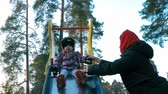 Mom puts on her mitten mitten little daughter in a colorful jacket that sits on a multicolored slide in the spring park against the backdrop of tall pines and knocking feet Stock Footage