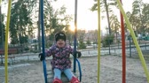 A little girl in a colorful pink jacket and black hat is riding on a swing over a puddle on the playground in the park-forest in early spring Stock Footage
