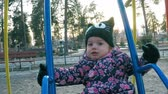 Little girl in a colorful pink jacket and black hat riding a swing on the playground in the park-forest in early spring Stock Footage