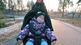 детский : Mom with a baby in a stroller walks in a park in early spring between puddles of melting snow in the background of the sunset Стоковые видеозаписи