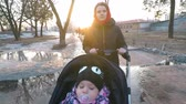 Mom with a baby in a stroller walks in a park in early spring between puddles of melting snow in the background of the sunset Stock Footage