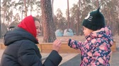 lipa : Little cute girl in a colorful pink jacket draws with a young mother with chalk on a pavement near the playground in a park on the outskirts of the forest during sunset in early spring