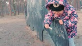 lipa : Little cute girl in a colorful pink jacket draws with chalk on a blackboard in the form of a dinosaur on a childrens playground in a park on the outskirts of the forest during sunset in early spring