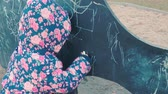 若い : Little cute girl in a colorful pink jacket draws with chalk on a blackboard in the form of a dinosaur on a childrens playground in a park on the outskirts of the forest during sunset in early spring