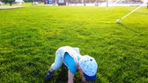 slzy : The kid clumsily walks on a bright green lawn and falls