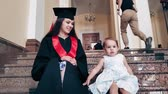 parke : Graduate girl with her child in the university corridor