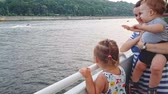 lancha : 4K. Mother with two children are floating on a boat on the wide river of the Dnieper and look overboard Vídeos