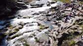 refrescar : Water stream flow among stones. Clear water quickly fall downhill flowing around dark wet stones. Close-up of waterfall pouring down black rocks. Beautiful mountain waterfall