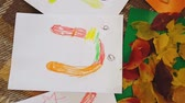 ウィーブ : Young mother and daughter draw oil pastels inscription Autumn on white sheets of paper and make an applique. Little girl with mom draw oil lettering Autumn inscription on white sheets of paper. 動画素材