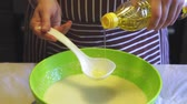 vasilha : Close-up slow motion of a female hand adds sunflower oil to batter in a green bowl in the home kitchen. Cooking pancakes
